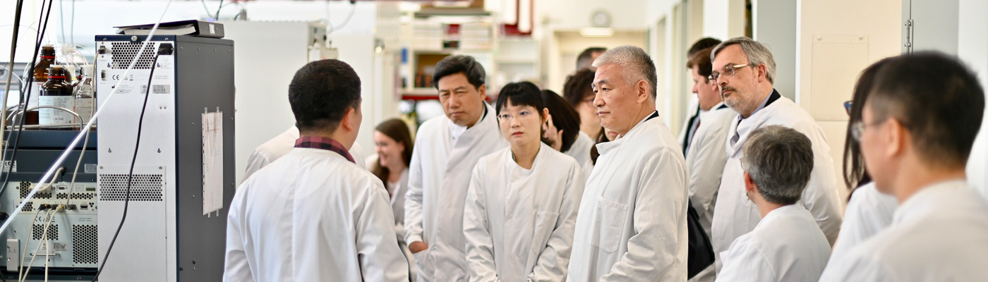 A group of people in white lab coats tour a scientific facility