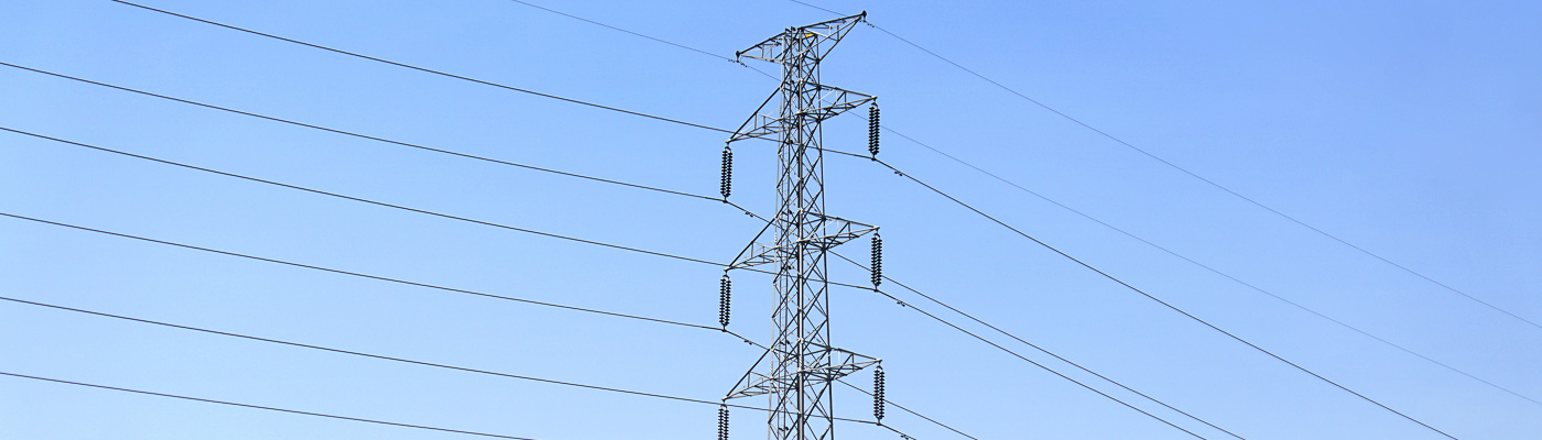 An electricity pylon against a blue sky