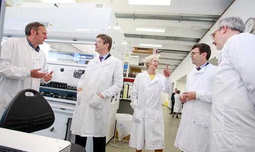A group of male and female scientists and businesspeople in white coats stand chatting.